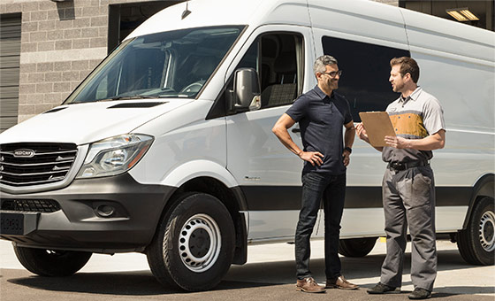 Two Men Standing Near a Sprinter Van