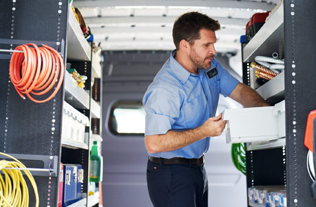 A man standing and working in the back of a Cargo Van