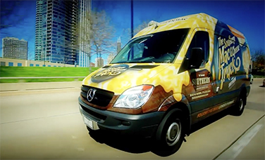 "A Sprinter Cargo Van with a ""The Southern Mac and Cheese Truck"" decal driving on the road"