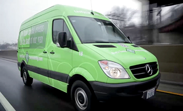 A green Sprinter Cargo Van driving on the road