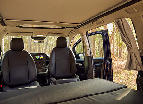 Interior view of the Metris Getaway van, with the back-seat bench converted into a bed.