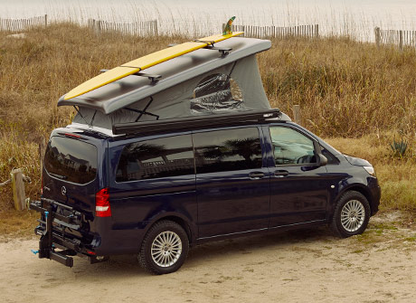 The Metris pop top camper van with top popped and a surfboard on the roof, parked near the beach.