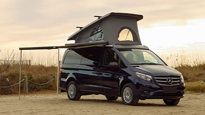 The Metris Getaway van with top popped and awning extending, parked at the beach at sunset.