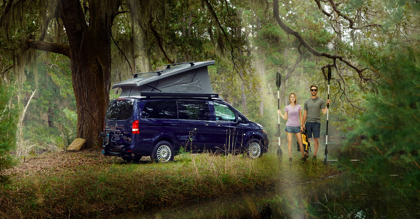 The Metris Getaway van with the top popped, parked by a couple standing next to a river.