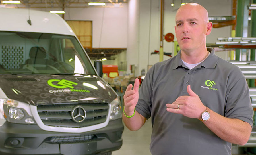 A man standing in front of a Mercedes-Benz van with a Corbins Electric decal