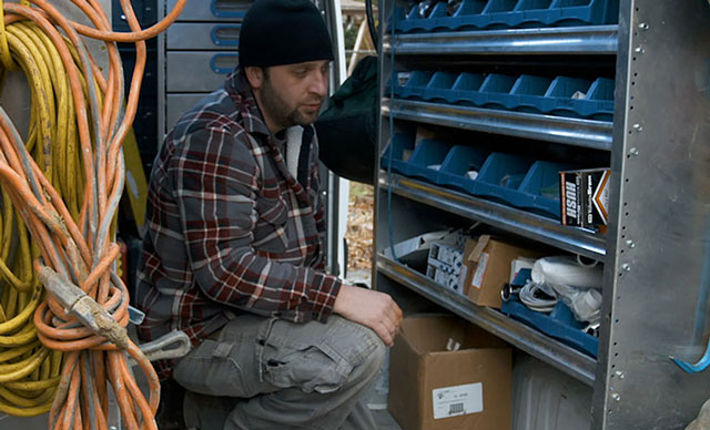 A plumber working from the back of a van