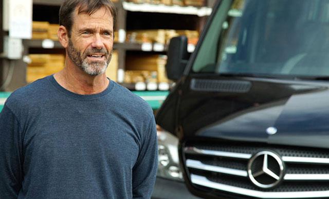 A man standing in front of a Mercedes-Benz van