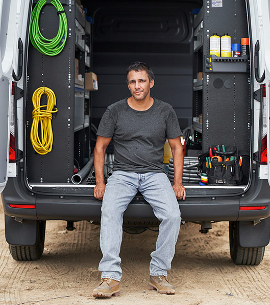 A man sitting on the back of an open Sprinter Cargo Van