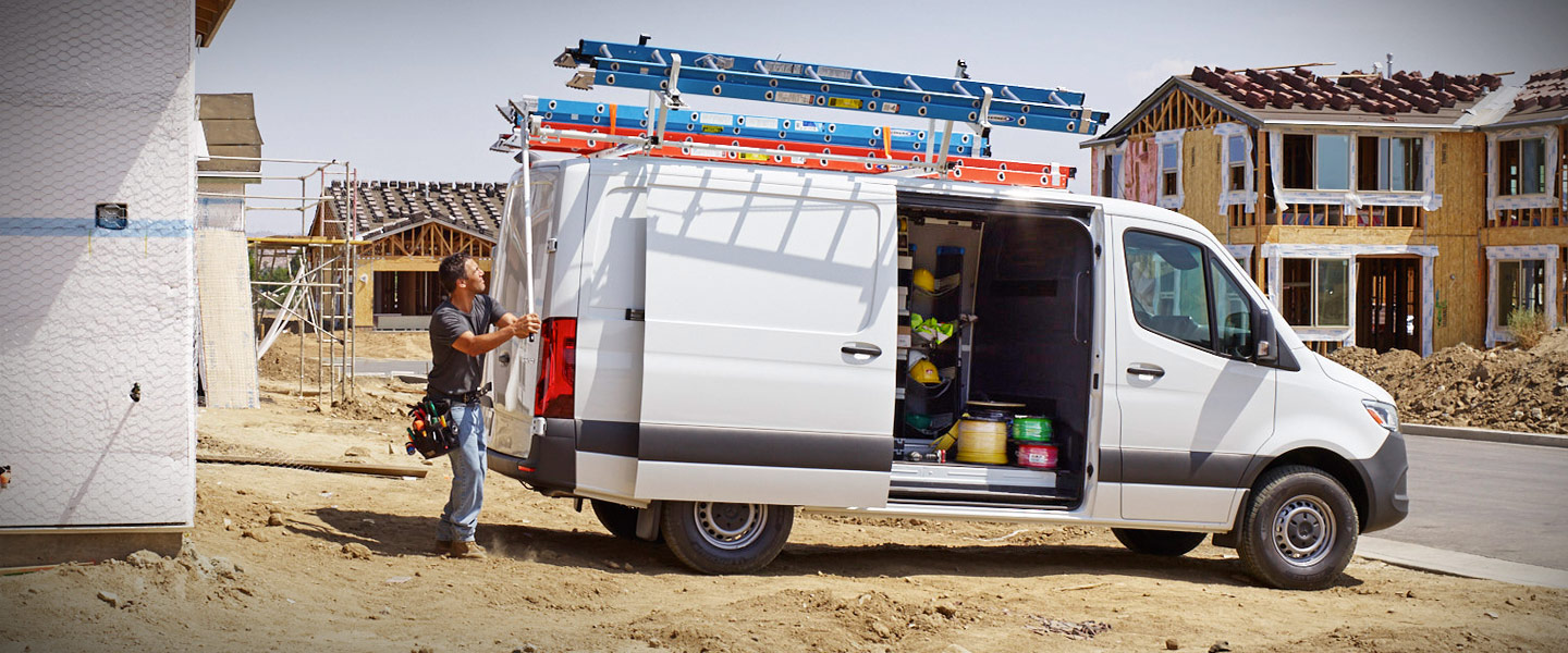 A man working from the back of a white Sprinter Cargo Van