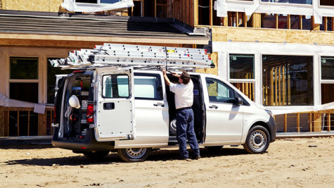 A man working by the side of a Metris Cargo Van at a construction site