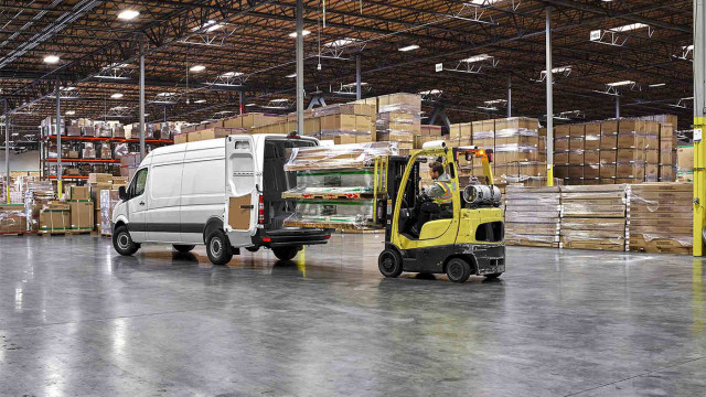 A forklift loading into a white Sprinter Cargo Van in a warehouse