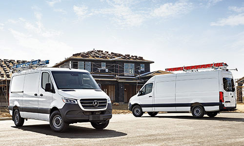 Two parked white Mercedes-Benz sprinter vans front and back views
